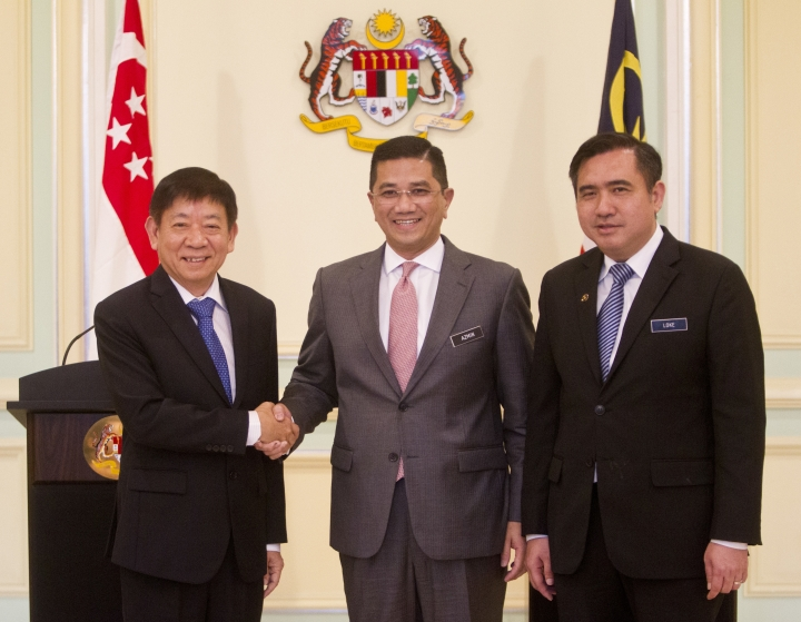 Malaysia's Minister of Economic Affair Mohamed Azmin Ali, center, and Minister for Infrastructure and Minister for Transport of Singapore Khaw Boon Wan, left, shake hands next to Malaysia's Minister of Transport Anthony Loke during a press conference at Prime Minister Office in Putrajaya, Malaysia, Wednesday, Sept. 5, 2018. A planned high-speed railway that would cut travel time between Kl and Singapore to just 90 minutes will now be deferred for two years, instead of being axed, the two governments said. (AP Photo/Yam G-Jun)