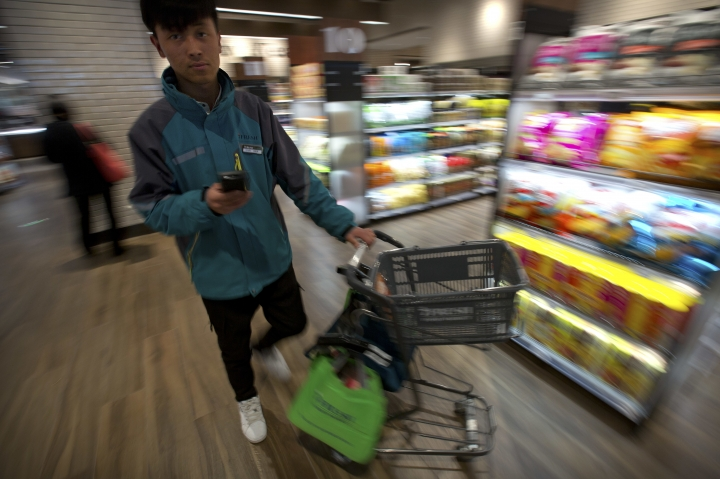 In this March 30, 2018, photo, a courier pushes a shopping cart as he fills an online order at a 7FRESH grocery store operated by Chinese e-commerce retailer JD.com in Beijing, China. The Chinese e-commerce billionaire who faces a possible rape accusation in Minneapolis built his business by promising honesty in a market plagued by fraud and fakes. (AP Photo/Mark Schiefelbein)