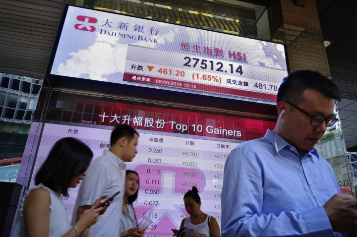 People stand in front of an electronic board showing Hong Kong share index outside a local bank in Hong Kong, Wednesday, Sept. 5, 2018. Asian stocks sank Wednesday after Wall Street declined on losses for tech and health care companies. (AP Photo/Vincent Yu)