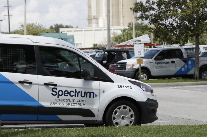 This Tuesday, Sept. 4, 2018, photo shows Charter Communications, Inc.'s Spectrum trucks in the parking lot at a Spectrum customer center in Orlando, Fla. Cable company Charter is launching a $45-a-month unlimited-data phone plan as cable companies try to diversify to offset slowing traditional cable TV revenue. (AP Photo/John Raoux)
