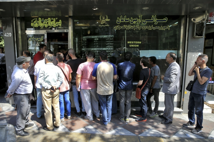 People line up in front of a currency exchange shop to buy U.S. dollars and euros, in downtown Tehran, Iran, Wednesday, Sept. 5, 2018. The Iranian rial fell Wednesday to its lowest rate on record and saw worried residents of Tehran line up outside of beleaguered moneychangers, part of a staggering 140-percent drop in the currency's value since America pulled out of the nuclear deal only four months ago. (AP Photo/Ebrahim Noroozi)