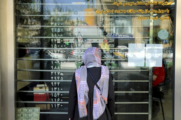 A woman checks various currency rates at an exchange shop window in downtown Tehran, Iran, Wednesday, Sept. 5, 2018. The Iranian rial fell Wednesday to its lowest rate on record and saw worried residents of Tehran line up outside of beleaguered moneychangers, part of a staggering 140-percent drop in the currency's value since America pulled out of the nuclear deal only four months ago. (AP Photo/Ebrahim Noroozi)