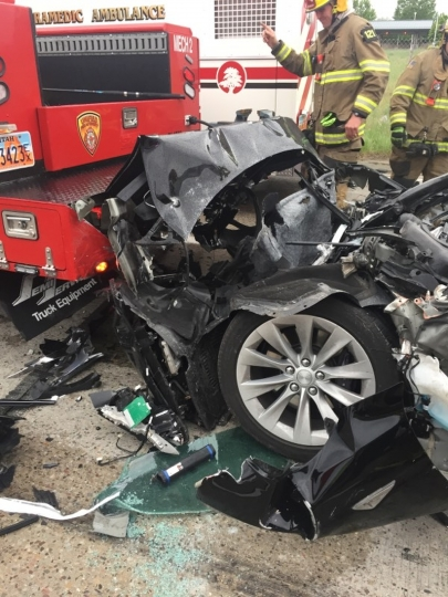 FILE - In this May 11, 2018, file photo, released by the South Jordan Police Department shows a traffic collision involving a Tesla Model S sedan with a fire department mechanic truck stopped at a red light in South Jordan, Utah. Heather Lommatzsch, the Utah driver who slammed her Tesla into the stopped firetruck at a red light while using the vehicle's semi-autonomous function, is suing the company. (South Jordan Police Department via AP, File)