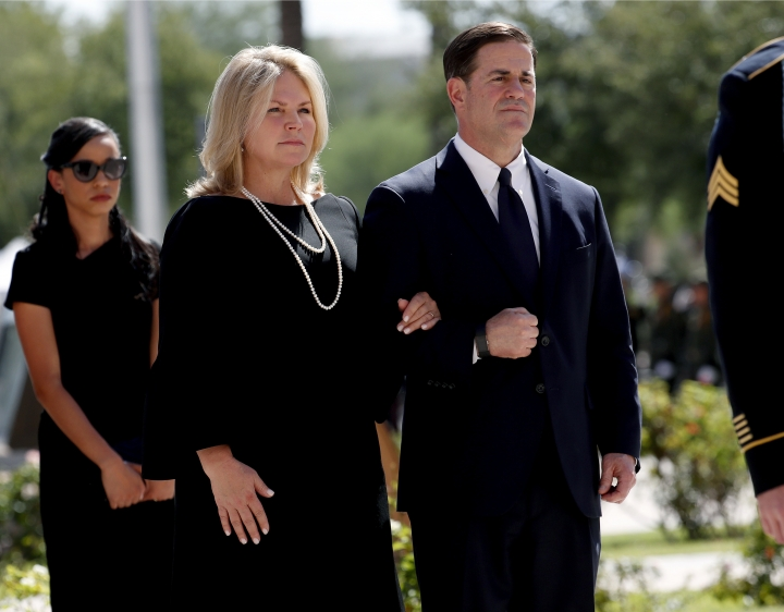 FILE - In this Aug. 29, 2018 file photo, Arizona Gov. Doug Ducey and his wife Angela Ducey, follow the casket of Sen. John McCain, R-Ariz., into a memorial service at the Capitol in Phoenix. Arizona has developed a reputation over the past decade for being one of the country's greatest political flashpoints, with divisive debates over immigration, rambunctious populists and a divided GOP. Ducey has navigated the state's political waters with a buttoned-down approach. The onetime chief executive officer of ice cream chain Cold Stone Creamery on Tuesday, Sept. 4, 2018, named former Sen. Jon Kyl to fill the seat vacated by the late John McCain. (AP Photo/Matt York, File)