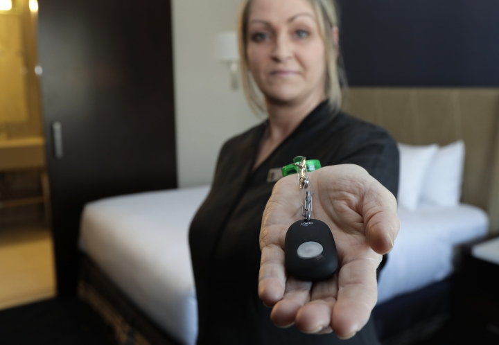 In this Wednesday, Sept. 5, 2018, photo Rani Accettola, a housekeeper at the Embassy Suites by Hilton hotel in Seattle's Pioneer Square neighborhood, poses for a photo while holding a device that lets her push a button and summon help if she is in a threatening situation while working in Seattle. (AP Photo/Ted S. Warren)