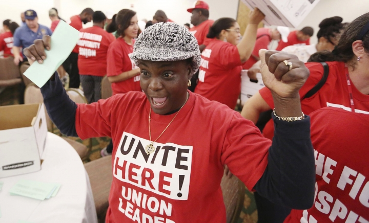 Marlene Philippe, a housekeeper for Disney, celebrates a union vote for a pay raise and bonus as ballots are counted at the Park Inn by Radisson in Kissimmee, Fla., on Thursday, Sept. 6, 2018. The vote tally comes after months of protests, negotiations and the rejection of a previous contract offer. (Stephen M. Dowell/Orlando Sentinel via AP)