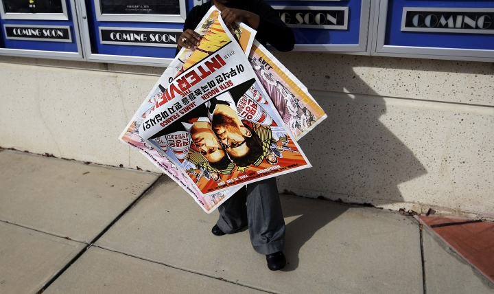 """FILE - In this Dec. 17, 2014, file photo, a poster for the movie """"The Interview"""" is carried away by a worker after being pulled from a display case at a Carmike Cinemas movie theater in Atlanta. A computer programmer working for the North Korean government was charged with devastating cyberattacks that hacked Sony Pictures Entertainment and unleashed the WannaCry ransomware virus that infected computers in 150 countries and crippled parts of the British health care system, federal prosecutors said Thursday, Sept. 6, 2018. U.S. officials believe the Sony hack was retribution for """"The Interview,"""" a comedy starring Seth Rogen and James Franco in a plot to assassinate North Korea's leader, Kim Jong Un. (AP Photo/David Goldman, File)"""