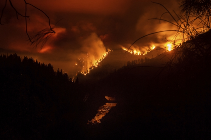 The Delta Fire burns in the Shasta-Trinity National Forest, Calif., on Wednesday, Sept. 5, 2018. Parked trucks lined more than two miles of Interstate 5 as both directions remained closed to traffic. (AP Photo/Noah Berger)