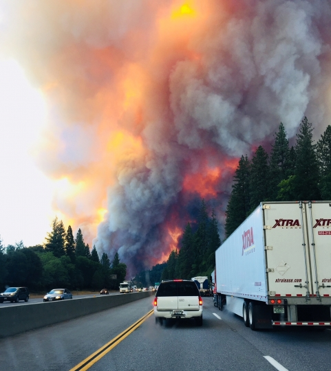 A fire rages as motorists travel on Interstate 5 near Lake Shasta, Calif., Wednesday, Sept. 5, 2018. (Jerri Tubbs via AP)