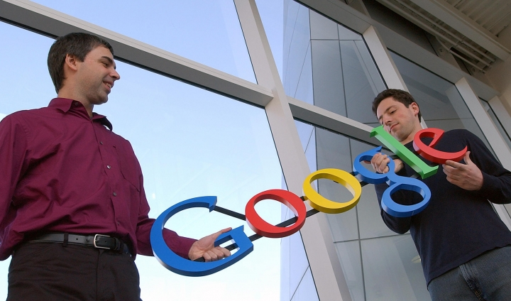 FILE- In this Jan. 15, 2004, file photo Google co-founders Larry Page, left, and Sergey Brin pose for a photo at their company's headquarters in Mountain View, Calif. Twenty years after Page and Brin set out to organize all of the internet's information, the search engine they named Google has morphed into a dominating force in smartphones, online video, email, maps and much more. (AP Photo/Ben Margot, File)