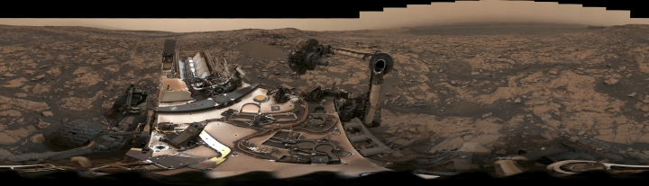 This composite image from Aug. 9, 2018 photos made available by NASA shows the Curiosity rover at Vera Rubin Ridge on Mars. A thin layer of dust is visible on the nuclear-powered rover, the result of a storm that enveloped the planet this summer. The darkish sky is from dust still in the atmosphere. (NASA/JPL-Caltech/MSSS via AP)