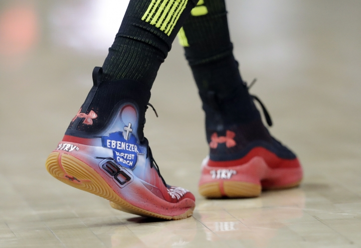 """FILE- In this Feb. 9, 2018, file photo Atlanta Hawks guard Kent Bazemore wears shoes with artwork depicting the Atlanta's historic Ebenezer Baptist Church during the first half of the team's NBA basketball game against the Cleveland Cavaliers in Atlanta. NBA players in recent years have worn shoes with messages of """"R.I.P. Trayvon Martin"""" and """"Sideline Racism"""" and images of Ebenezer Baptist Church, where the Rev. Martin Luther King Jr. preached. (AP Photo/John Bazemore, File)"""