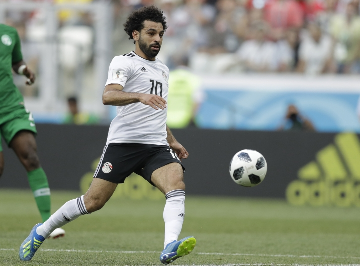 FILE - In this June 25, 2018 file photo, Egypt's Mohamed Salah chases the ball during the group A match between Saudi Arabia and Egypt at the 2018 soccer World Cup at the Volgograd Arena in Volgograd, Russia. The Pharaohs have at last given Egyptians something to cheer about and, not surprisingly, Liverpool's Salah played a big part in it. A record seven-time African champion, the Pharaohs thrashed Niger 6-0 in African Cup of Nations qualifying on Saturday, Sept. 8, 2018, their first competitive match since their miserable run in the World Cup in Russia where the team lost all three group matches. (AP Photo/Andrew Medichini, File)