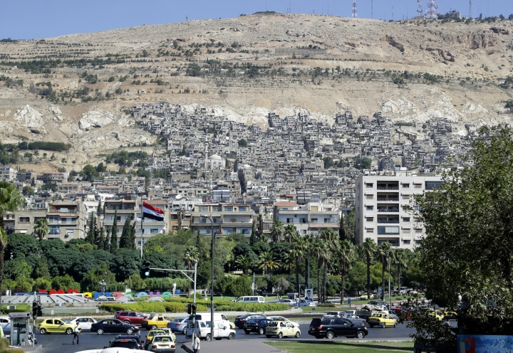 FILE - In this Aug. 13, 2018 photo taken through a bus window Syrians drive their cars in front of residential buildings in Damascus, Syria. A new Syrian law empowering the government to confiscate property is threatening to leave refugees stuck in Europe with no homes to return to. (AP Photo/Sergei Grits)