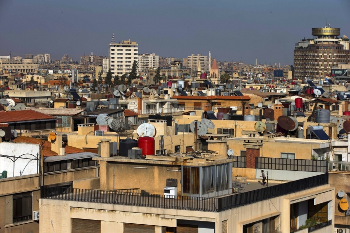 FILE - In this Feb. 28, 2016 file photo a Syrian boy plays soccer on the roof of a building in Damascus, Syria. A new Syrian law empowering the government to confiscate property is threatening to leave refugees stuck in Europe with no homes to return to. (AP Photo/Hassan Ammar, file)