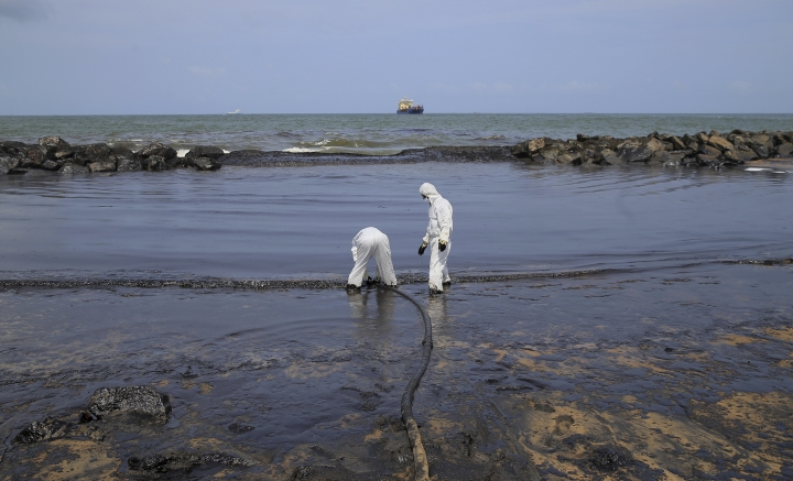 Sri Lankan coast guard personnel in protective clothes work to remove oil from a beach following an oil spill in Uswetakeiyawa, a coastal town north of Colombo, Sri Lanka, Monday, Sept. 10, 2019.Sri Lanka deployed hundreds of coast guard and navy personnel on Monday to clean oil slicks on a coastal stretch near the capital following a spill caused by a pipeline leak. (AP Photo/Eranga Jayawardena)
