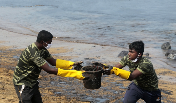 Sri Lankan army soldiers remove oil slick and sand from a beach following an oil spill in Uswetakeiyawa, a coastal town north of Colombo, Sri Lanka, Monday, Sept. 10, 2019.Sri Lanka deployed hundreds of coast guard and navy personnel on Monday to clean oil slicks on a coastal stretch near the capital following a spill caused by a pipeline leak. (AP Photo/Eranga Jayawardena)
