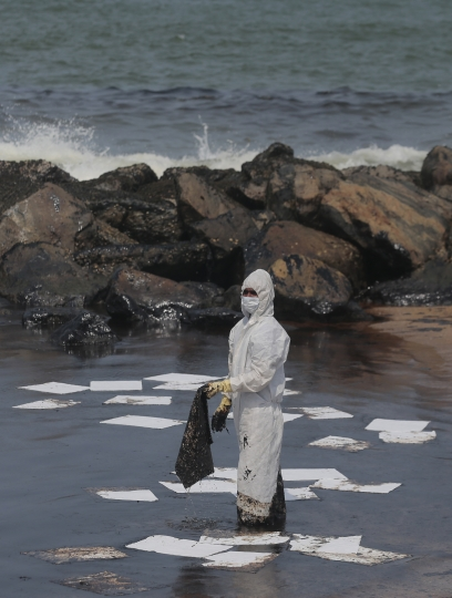 A Sri Lankan coast guard person in protective clothes works to remove oil from a beach following an oil spill in Uswetakeiyawa, a coastal town north of Colombo, Sri Lanka, Monday, Sept. 10, 2019.Sri Lanka deployed hundreds of coast guard and navy personnel on Monday to clean oil slicks on a coastal stretch near the capital following a spill caused by a pipeline leak. (AP Photo/Eranga Jayawardena)