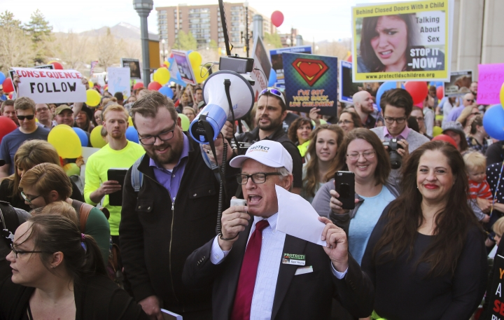 FILE - In this March 30, 2018, file photo, Sam Young, center, speaks to a group of people during a march to church headquarters, in Salt Lake City. Young, a Mormon who has led a campaign criticizing the church's practice of allowing closed-door, one-on-one interviews of youth by lay leaders, will have to wait to find out if he'll be kicked out of the religion. Young said late Sunday, Sept. 9, 2018, that local church leaders didn't make a decision following a disciplinary council at his congregation in Houston. Young says they didn't say when they will decide. (AP Photo/Rick Bowmer, File)