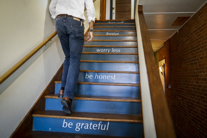"""Michael Koveleski climbs the stairs at his store Design Sleepin Yellow Springs, Ohio on Thursday, Aug. 23, 2018. """"You're only going to change your life when things are bad _ or terrible,"""" Michael says. """"Our thing was 9/11, starting over with nothing. ... I am thrilled at the way it came out to be."""" (AP Photo/John Minchillo)"""