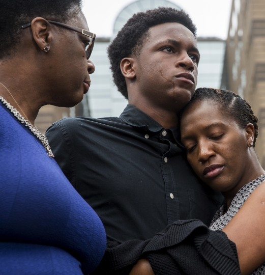 Brandt Jean, brother of Botham Jean, is comforted by his sister, Allisa Charles-Findley, as their mother, Allison, looks on during a news conference on Monday, Sept. 10, 2018, at the Frank Crowley Courts Building in Dallas. Botham Jean was shot and killed by Dallas police officer Amber Guyger in his apartment on Thursday night. (Shaban Athuman/The Dallas Morning News via AP)
