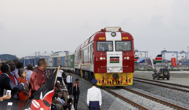 FILE - In this May 30, 2017, file photo, Kenyan President Uhuru Kenyatta, 3rd left, watches during the opening of the SGR cargo train runs on a China-backed railway from the port containers depot in Mombasa Kenya, to Nairobi. A wave of Chinese-financed railways and other trade links in Africa and Asia that have prompted worries about debt and Beijing's ambitions is reducing politically dangerous inequality between regions within countries, a multinational group of researchers said Tuesday, Sept. 11, 2018. (AP Photo/Khalil Senosi, File)