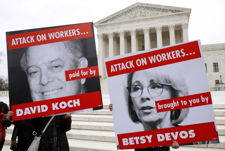 FILE - In this Monday, Feb. 26, 2018, file photo, Members of the American Federation of Teachers hold up signs depicting Education Secretary Betsy DeVos and Koch brother, David Koch, while protesting in support of unions outside of the Supreme Court in Washington. A U.S. appeals court says California's attorney general can collect the names and addresses of top donors to two conservative non-profit groups, including one with links to the billionaire Koch brothers. A three-judge panel of the 9th U.S. Circuit Court of Appeals said Tuesday, Sept. 11, 2018, the information from Americans for Prosperity Foundation and Thomas More Law Center serve the important state goal of preventing charities from committing fraud. (AP Photo/Jacquelyn Martin, File)