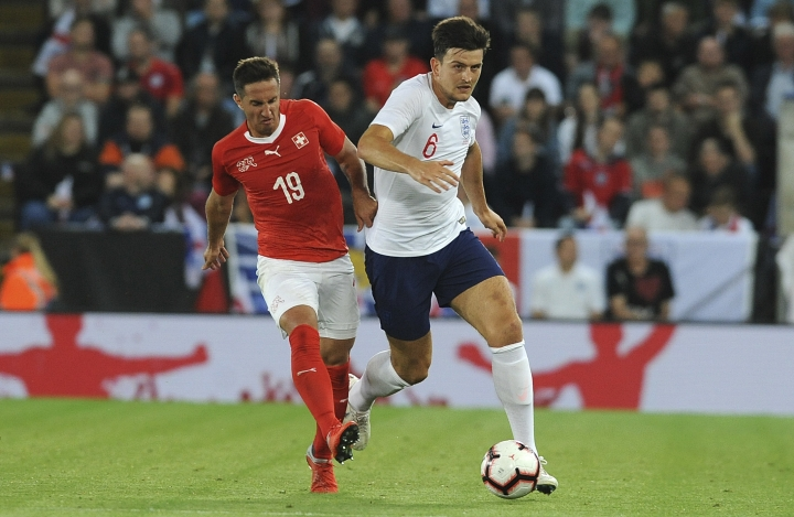 Switzerland's Mario Gavranovic, left, and England's Harry Maguire challenge for the ball during the International friendly soccer match between England and Switzerland at the King Power Stadium in Leicester, England, Tuesday, Sept. 11, 2018 . (AP Photo/ Rui Vieira)