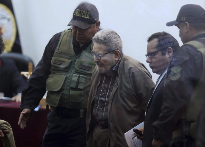 In this photo taken through a window, Abimael Guzman, founder and leader of the Shining Path guerrilla movement, arrives to court at a military base in Callao, Peru, Tuesday, Sept. 11, 2018. On Tuesday, the historic leader of the terrorist group Shining Path will be sentenced for his role in a 1992 car bomb that killed 25 people in Lima. (AP Photo/Martin Mejia)