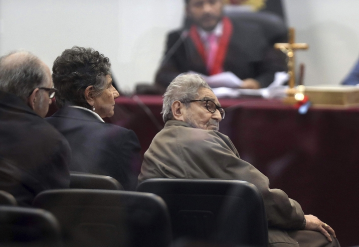 In this photo taken through a window, Abimael Guzman, founder and leader of the Shining Path guerrilla movement, looks at his lawyer while siting with his partner Elena Iparraguirre, during the sentencing phase of their trial at a naval base in Callao, Peru, Tuesday, Sept. 11, 2018. On Tuesday, the historic leader of the terrorist group Shining Path and Iparraguirre will be sentenced for their role in a 1992 car bomb that killed 25 people in Lima. (AP Photo/Martin Mejia)