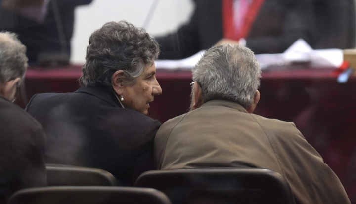 In this photo taken through a window, Abimael Guzman, founder and leader of the Shining Path guerrilla movement, right, listens to his partner Elena Iparraguirre during the sentencing phase of their trial at a naval base in Callao, Peru, Tuesday, Sept. 11, 2018. On Tuesday, the historic leader of the terrorist group Shining Path and Iparraguirre will be sentenced for their role in a 1992 car bomb that killed 25 people in Lima. (AP Photo/Martin Mejia)