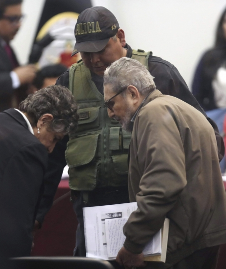 In this photo taken through a window, Abimael Guzman, founder and leader of the Shining Path guerrilla movement, right, arrives to court alongside his partner Elena Iparraguirre during the sentencing phase of their trial at a naval base in Callao, Peru, Tuesday, Sept. 11, 2018. On Tuesday, the historic leader of the terrorist group Shining Path and Iparraguirre will be sentenced for their role in a 1992 car bomb that killed 25 people in Lima. (AP Photo/Martin Mejia)