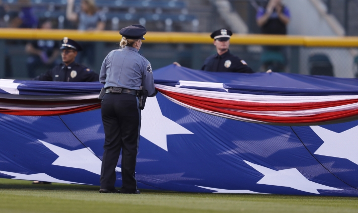 Police officers unfurl an American flag to mark the anniversary of the 9/11 terrorist attacks during a ceremony before a baseball game against the Arizona Diamondbacks, Tuesday, Sept. 11, 2018, in Denver. (AP Photo/David Zalubowski)