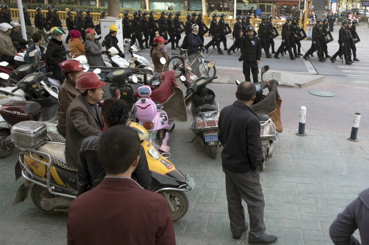FILE - In this Nov. 5, 2017 file photo, residents watch a convoy of security personnel in a show of force through central Kashgar in western China's Xinjiang region. Two U.S. lawmakers are urging the extension of American export restrictions to prevent sales of equipment that could be used in China's massive security clampdown targeting the Xinjiang region's native Muslim population. Sen. Marco Rubio and Rep. Chris Smith said in a letter, Wednesday, Sept. 12, 2018, to the U.S. commerce secretary that they want foreign entities, including businesses, research institutions, government and private organizations, and individuals seen as profiting from the clampdown added to a watch list. (AP Photo/Ng Han Guan, File)