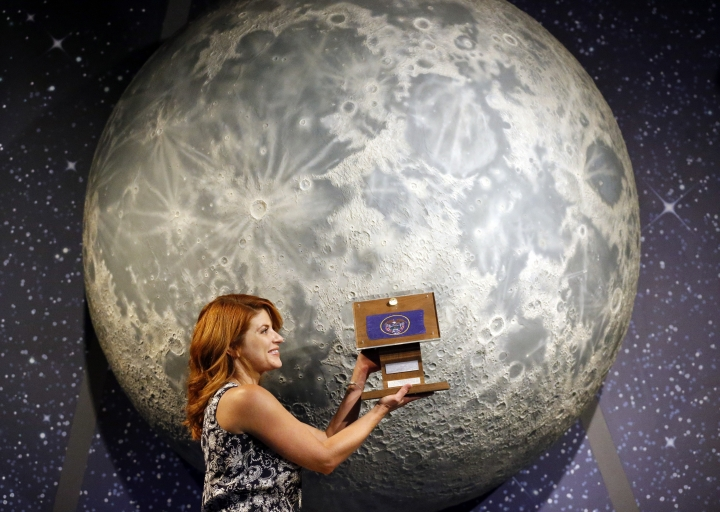 In this Thursday, Aug. 23, 2018, photo, Lindsie Smith, from the Clark Planetarium, holds moon rocks encased in acrylic and mounted on a wooden plaque at the Clark Planetarium, in Salt Lake City. A former NASA investigator who has spent more than a decade tracking missing moon rocks is closing in on his goal of finding all 50 lunar samples gifted to U.S. states after Neil Armstrong's first steps on the moon. In recent weeks, two more of the moon rocks that dropped off the radar after the 1969 Apollo 11 mission have been located in Louisiana and Utah. (AP Photo/Rick Bowmer)