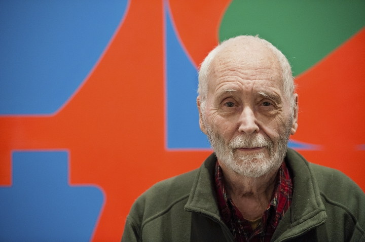 FILE - In this Sept. 24, 2013, file photo, artist Robert Indiana, known for his LOVE artwork, poses in front of that painting at New York's Whitney Museum of American Art. A lawsuit accusing several people of taking advantage of Indiana before his death must be sorted out before the estate can proceed with plans for a museum showing his artwork. On Wednesday, Sept. 12, 2018, attorneys for the pop artist questioned those close to Indiana about his assets, now valued at $60 million. (AP Photo/Lauren Casselberry, File)