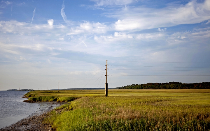 FILE - In this May 16, 2013, file photo, a utility pole stands in the middle of a marsh at sunset on Sapelo Island, Ga., a Gullah-Geechee community. A tight-knit community of slave descendants on the South Carolina coast is used to riding out big storms, from a storm that killed an estimated 2,000 people in 1893 to Tropical Storm Irma last year. (AP Photo/David Goldman, File)