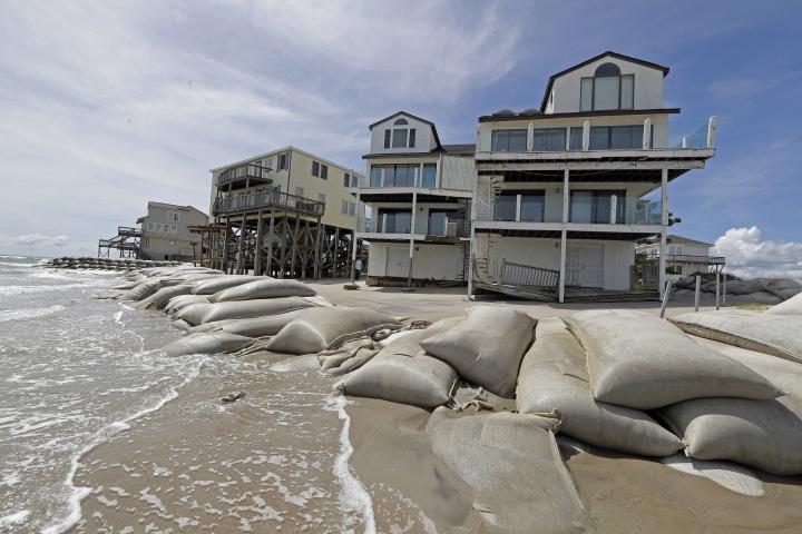 Sand bags surround homes on North Topsail Beach, N.C., Wednesday, Sept. 12, 2018, as Hurricane Florence threatens the coast. (AP Photo/Chuck Burton)