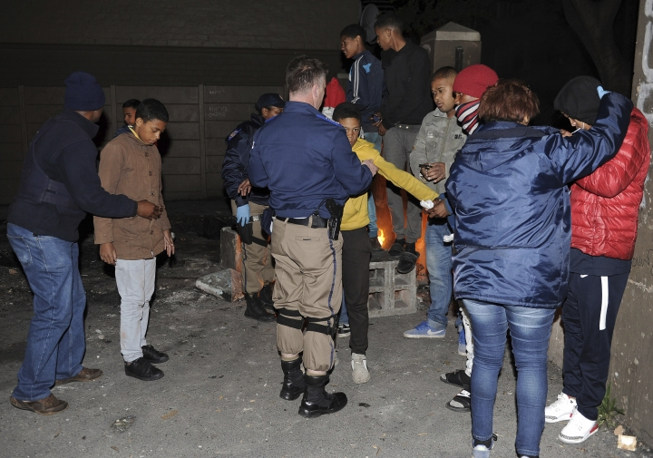 In this photo taken Friday, Aug. 17, 2018, police search suspects for guns and drugs during a raid on a known drug house in Mannenburg, Cape Town, South Africa. As gunshots ring out in one of South Africa's most dangerous neighborhoods, a new technology detects the gun's location and immediately alerts police. (AP Photo/Nasief Manie)