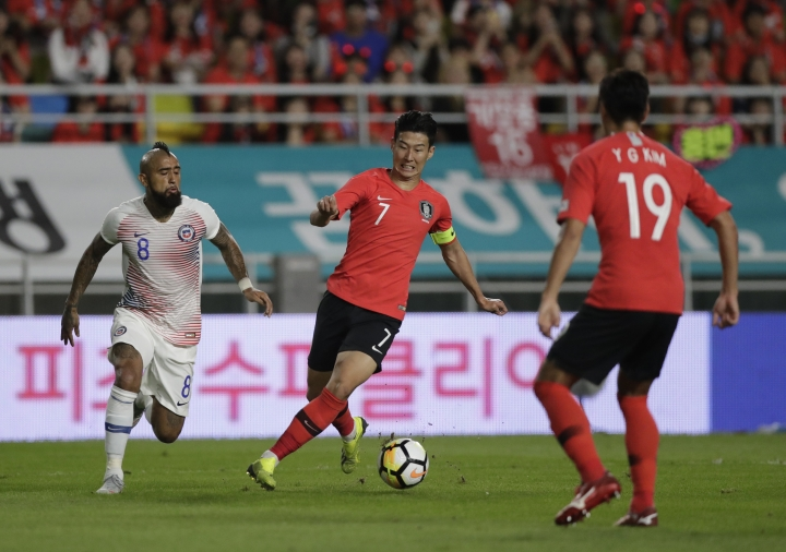 South Korea's Son Heung-min, center, and Chile's Artuso Vidal, left, fight for the ball during a friendly soccer match between South Korea and Chile at Suwon World Cup Stadium in Suwon, South Korea, Tuesday, Sept. 11, 2018. (AP Photo/Lee Jin-man)