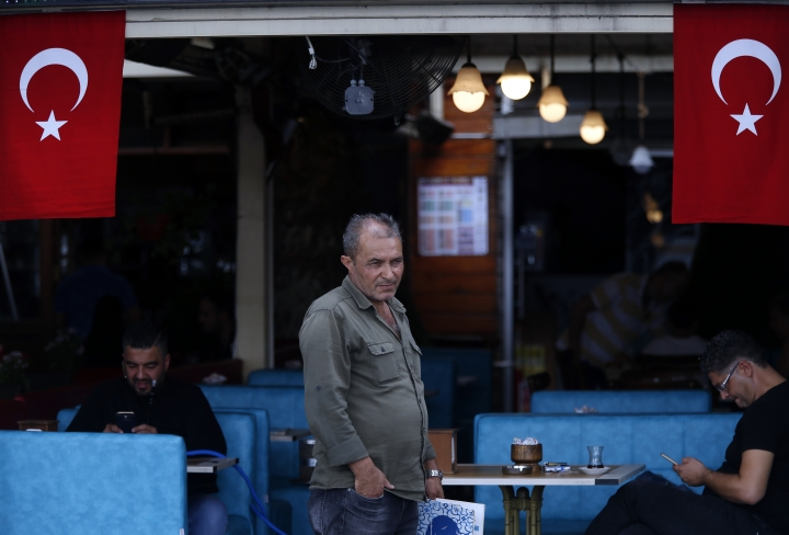 A restaurant worker waits for customers in Istanbul, Thursday, Sept. 13, 2018. Turkey's central bank on Thursday raised its key interest rate sharply to contain inflation and support the currency after steep declines this year, despite President Recep Tayyip Erdogan's comments earlier opposing any rate hikes. The currency had plunged some 40 percent against the dollar this year.(AP Photo/Lefteris Pitarakis)