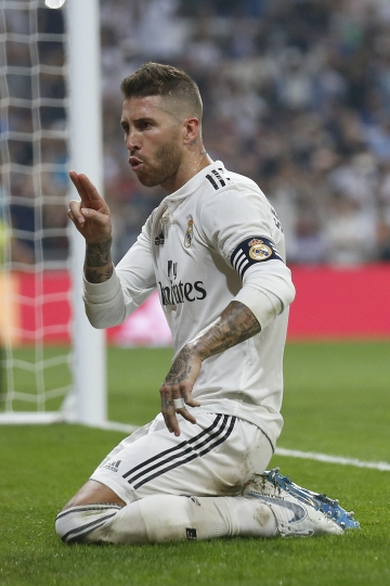Real Madrid's Sergio Ramos celebrates in front of a TV camera after scoring a penalty and his team's fourth goal during the Spanish La Liga soccer match between Real Madrid and Leganes at the Santiago Bernabeu stadium in Madrid, Saturday, Sep. 1, 2018. (AP Photo/Andrea Comas)