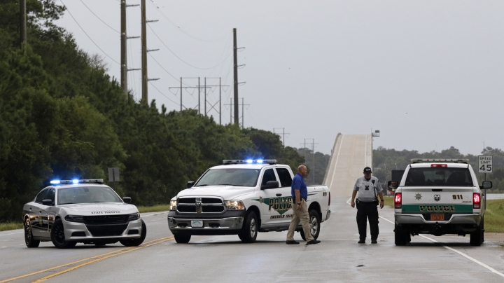 Police officers have the road leading to Emerald Isle blocked off to traffic as Hurricane Florence starts to hit Emerald Isle N.C., Thursday, Sept. 13, 2018. (AP Photo/Tom Copeland)