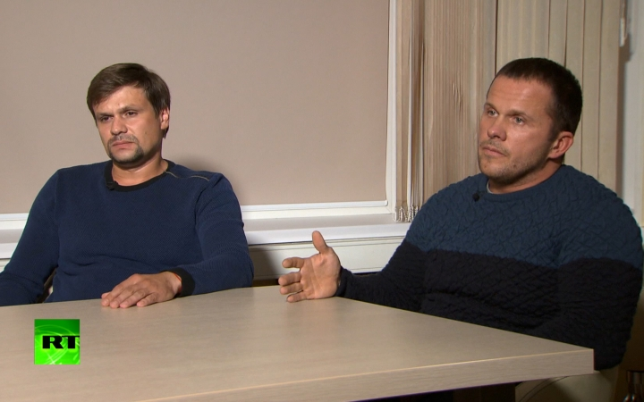 In this video grab provided by the RT channel , Ruslan Boshirov, left, and Alexander Petrov attend their first public appearance in an interview with the Kremlin-funded RT channel in Moscow, Russia, Thursday, Sept. 13, 2018. The two Russian men charged in Britain with poisoning a former Russian spy with a deadly nerve agent appeared on Russian television on Thursday, saying they visited the suspected crime scene as tourists. (RT channel video via AP)
