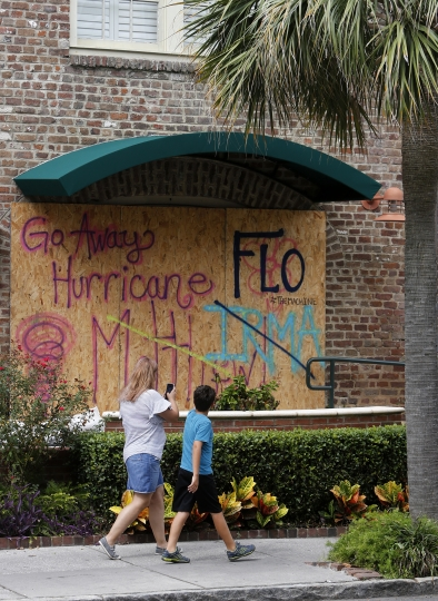 Pedestrians pass a sign at the Harbour View Inn asking for Hurricane Florence to spare the Lowcountry in Charleston, S.C., as Hurricane Florence spins out in the Atlantic ocean Thursday, Sept. 13, 2018. (AP Photo/Mic Smith)