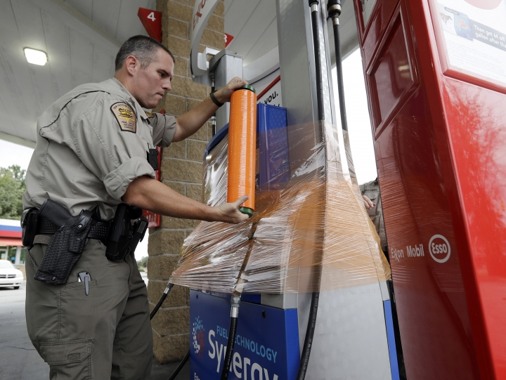 New Hanover Sheriff's deputy J. Brown wraps a gas pump for protection in Wilmington, N.C., as Hurricane Florence threatens the coast Thursday, Sept. 13, 2018. (AP Photo/Chuck Burton)
