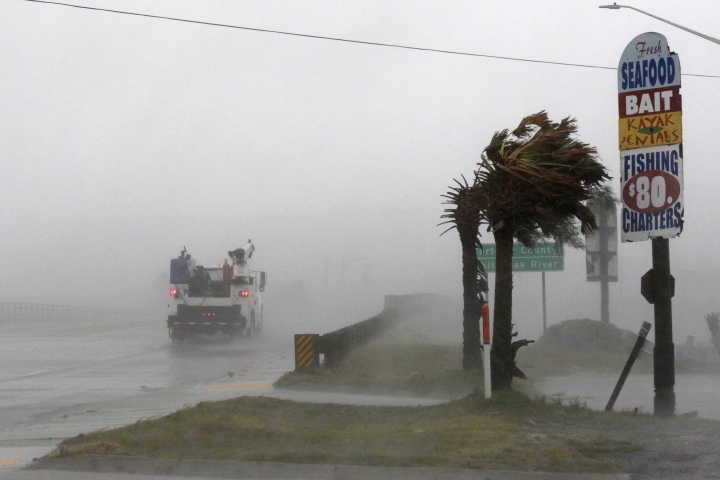 A work truck drives on Hwy 24 as the wind from Hurricane Florence blows palm trees in Swansboro N.C., Thursday, Sept. 13, 2018. (AP Photo/Tom Copeland)