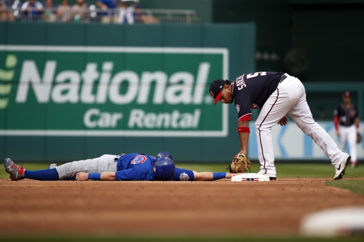 Chicago Cubs' Ian Happ, left, is out at second on being tagged by Washington Nationals second baseman Adrian Sanchez (5) during the third inning of a baseball game, Thursday, Sept. 13, 2018, at Nationals Park in Washington. (AP Photo/Jacquelyn Martin)