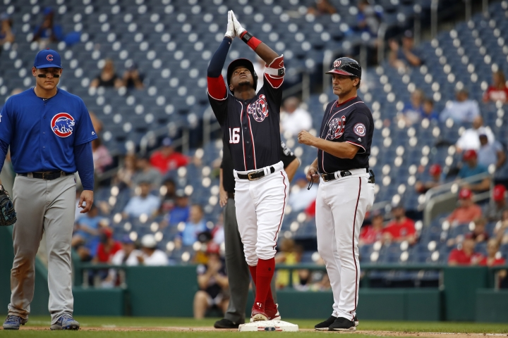 Chicago Cubs first baseman Anthony Rizzo (44), left, and Washington Nationals' first base coach Tim Bogar, right, look on as Nationals' Victor Robles (16) reacts after getting safely to first after batting in the third inning of a baseball game against the Chicago Cubs, Thursday, Sept. 13, 2018, in Washington. (AP Photo/Jacquelyn Martin)