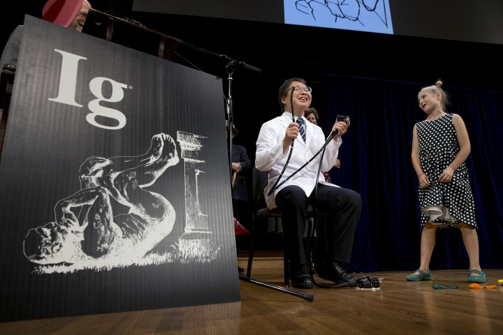 Akira Horiuchi, center, of Japan, who won the Ig Nobel in medical education demonstrates his self colonoscopy technic as Miss Sweetie Poo, right, attempts to cut him off for going over his allotted time during award ceremonies at Harvard University in Cambridge, Mass., Thursday, Sept. 13, 2018.(AP Photo/Michael Dwyer)